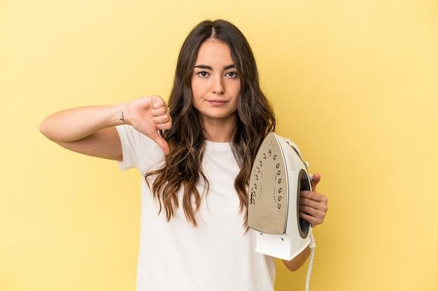 嫌いなジェスチャーを示す黄色の背景に分離された鉄を保持している若い白人女性は、親指を下に向けます。不一致の概念。