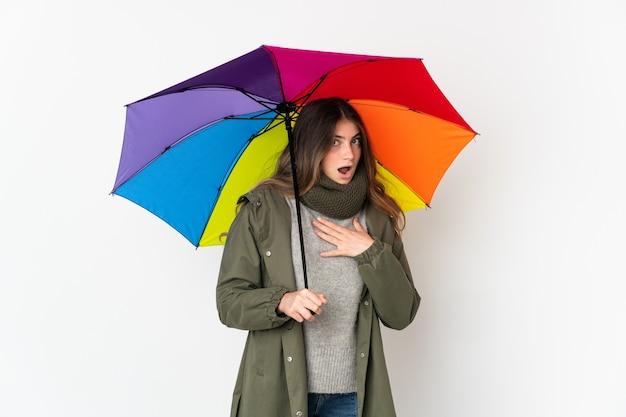 Молодая кавказская женщина, держащая зонтик на белом фоне, удивлена и шокирована, глядя вправо