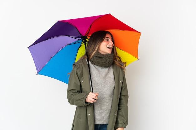 측면 위치에서 웃고 흰색에 고립 된 우산을 들고 젊은 백인 여자
