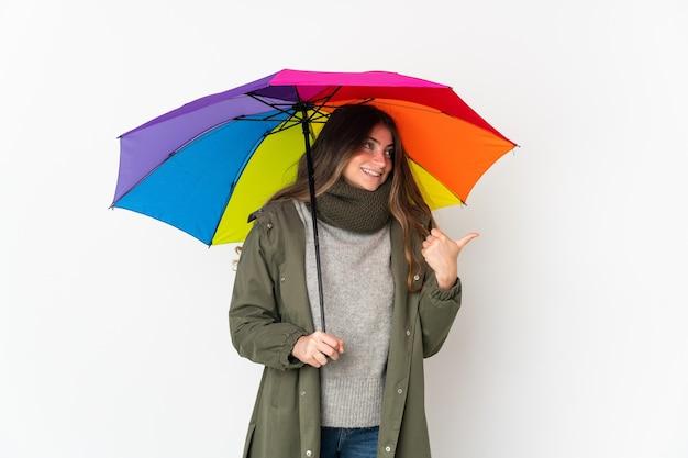 제품을 제시하기 위해 측면을 가리키는 흰색에 고립 된 우산을 들고 젊은 백인 여자