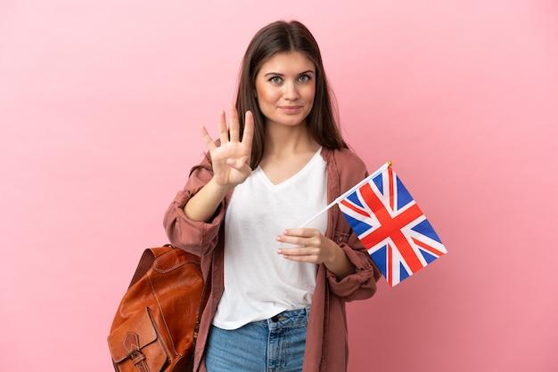 Молодая кавказская женщина, держащая флаг соединенного королевства, изолирована счастливой и считает четыре пальцами