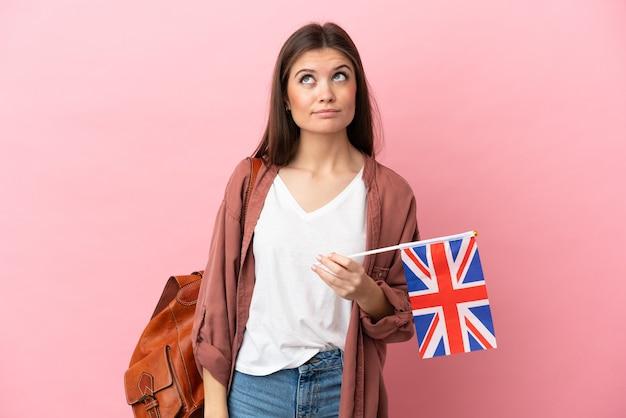 분홍색 배경에 고립 된 영국 국기를 들고 찾고 젊은 백인 여자
