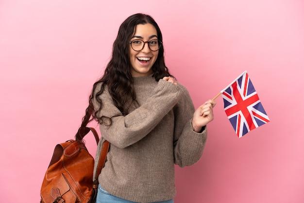 勝利を祝うピンクの背景に分離されたイギリスの旗を保持している若い白人女性