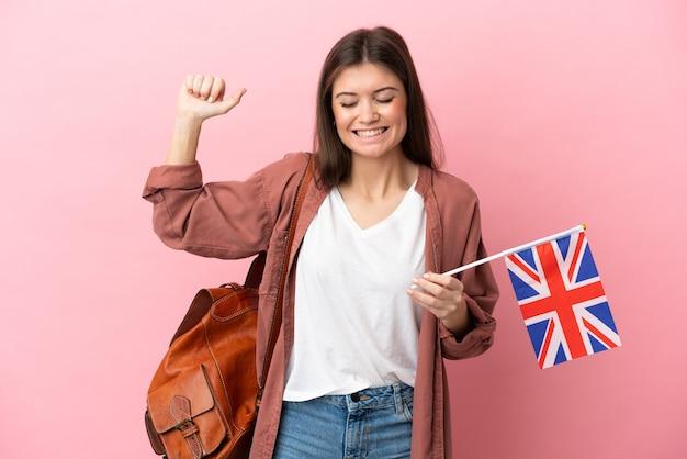강한 제스처를 하 고 분홍색 배경에 고립 된 영국 국기를 들고 젊은 백인 여자