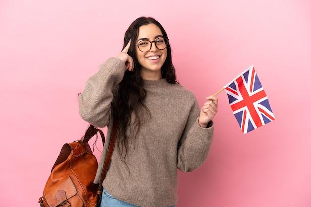疑いと思考を持っているピンクの背景に分離されたイギリスの旗を保持している若い白人女性