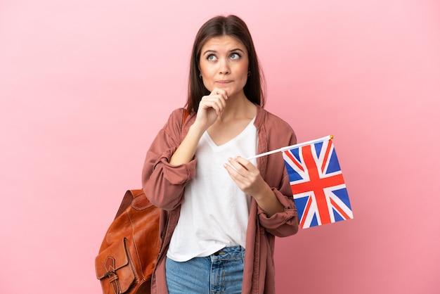 의심과 생각을 갖는 분홍색 배경에 고립 된 영국 국기를 들고 젊은 백인 여자