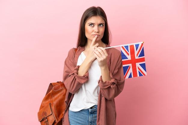찾는 동안 의심을 갖는 분홍색 배경에 고립 된 영국 국기를 들고 젊은 백인 여자