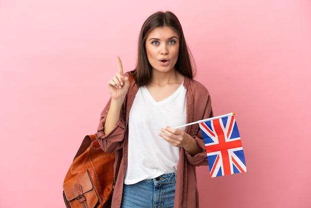 분홍색 배경에 고립 된 영국 국기를 들고 젊은 백인 여자는 손가락을 들어 올리는 동안 솔루션을 실현하려는 의도