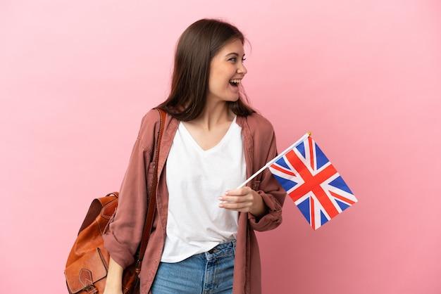 Молодая кавказская женщина, держащая флаг соединенного королевства, изолированная на розовом фоне, смеется в боковом положении