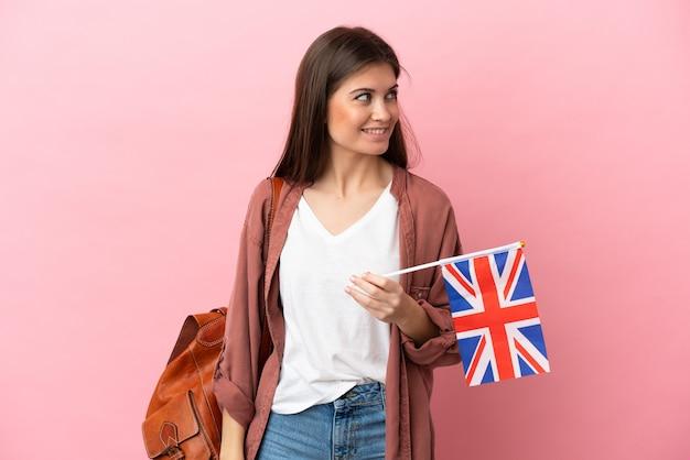 영국 국기를 들고 젊은 백인 여자 측면을 찾고 웃고 분홍색 배경에 고립
