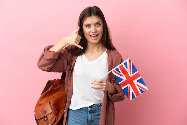 전화 제스처를 만드는 분홍색 배경에 고립 된 영국 국기를 들고 젊은 백인 여자. 나에게 다시 전화