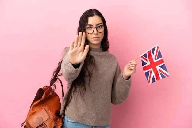 중지 제스처를 만드는 분홍색 배경에 고립 된 영국 국기를 들고 젊은 백인 여자