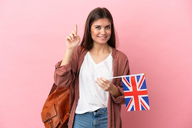 Молодая кавказская женщина держит флаг соединенного королевства на розовом фоне, указывая на отличную идею
