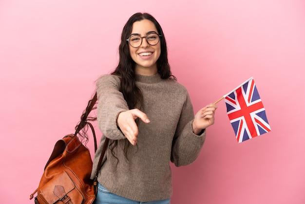 좋은 거래를 닫기 위해 악수하는 분홍색 배경에 고립 된 영국 국기를 들고 젊은 백인 여자