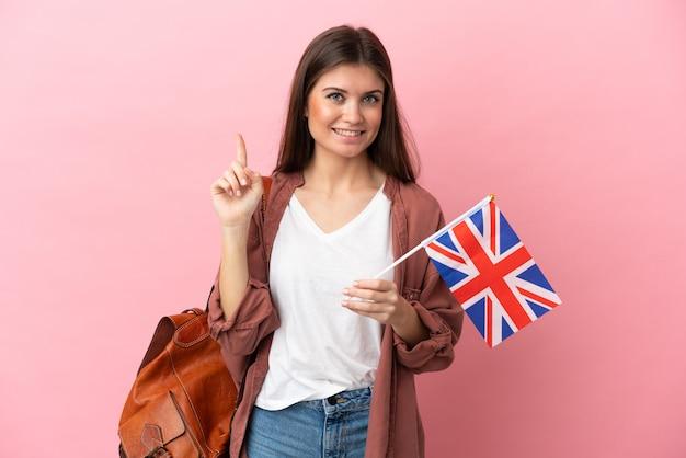Молодая кавказская женщина, держащая флаг соединенного королевства на розовом фоне, показывает и поднимает палец в знак лучших