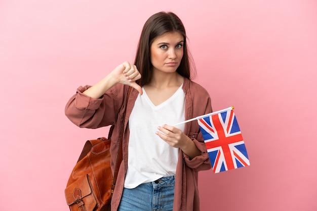 부정적인 표현으로 아래로 엄지 손가락을 보여주는 분홍색 배경에 고립 된 영국 국기를 들고 젊은 백인 여자