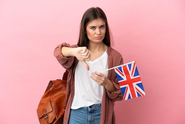 부정적인 표정으로 엄지손가락을 아래로 보여주는 분홍색 배경에 고립 된 영국 국기를 들고 젊은 백인 여자