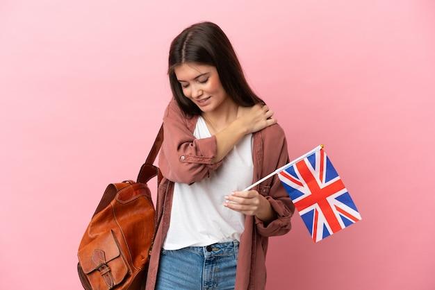 노력을 한 데 대한 어깨에 통증을 앓고 분홍색 배경에 고립 된 영국 국기를 들고 젊은 백인 여자