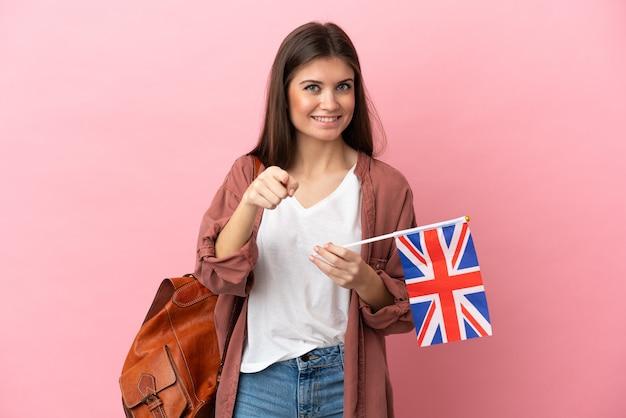 Молодая кавказская женщина, держащая флаг соединенного королевства, изолированная на розовом фоне, удивлена и указывает вперед