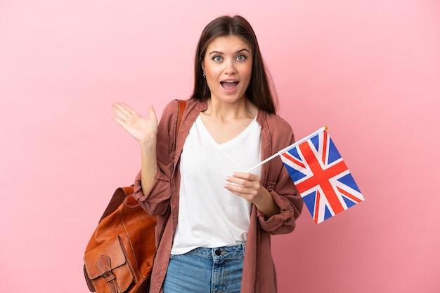충격 된 표정으로 분홍색 배경에 고립 된 영국 국기를 들고 젊은 백인 여자