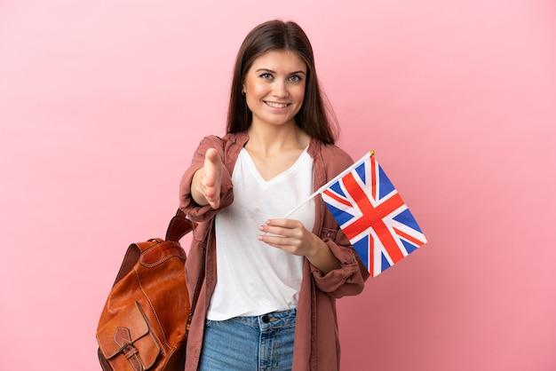 좋은 거래를 닫기 위해 악수하는 분홍색 벽에 고립 된 영국 국기를 들고 젊은 백인 여자