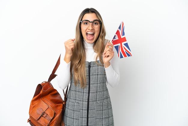 승자 위치에서 승리를 축하하는 흰색 배경에 고립 된 영국 국기를 들고 젊은 백인 여자