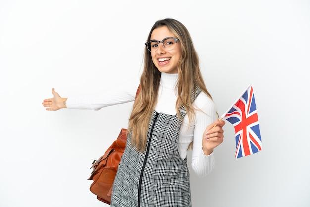 Молодая кавказская женщина держит флаг соединенного королевства на белом фоне, протягивая руки в сторону, приглашая приехать