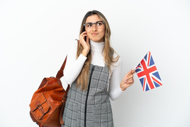 Молодая кавказская женщина, держащая флаг соединенного королевства на белом фоне, разочарована и закрывает уши
