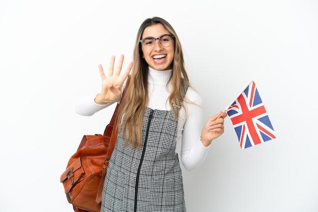 Молодая кавказская женщина держит флаг соединенного королевства, изолированные на белом фоне, счастлива и считает четыре пальцами