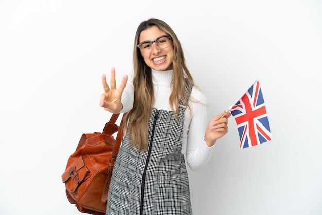 幸せな白い背景で隔離のイギリス国旗を保持し、指で3を数える若い白人女性