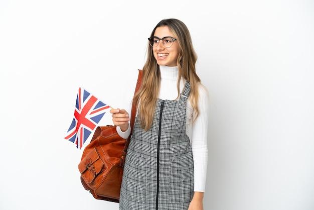 측면을 찾고 흰색 배경에 고립 된 영국 국기를 들고 젊은 백인 여자
