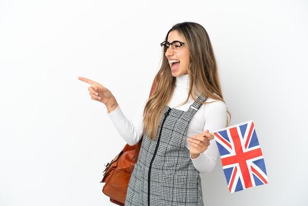 Молодая кавказская женщина держит флаг соединенного королевства на белом фоне, указывая пальцем в сторону и представляет продукт
