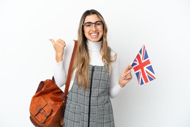 Молодая кавказская женщина держит флаг соединенного королевства на белом фоне, указывая в сторону, чтобы представить продукт