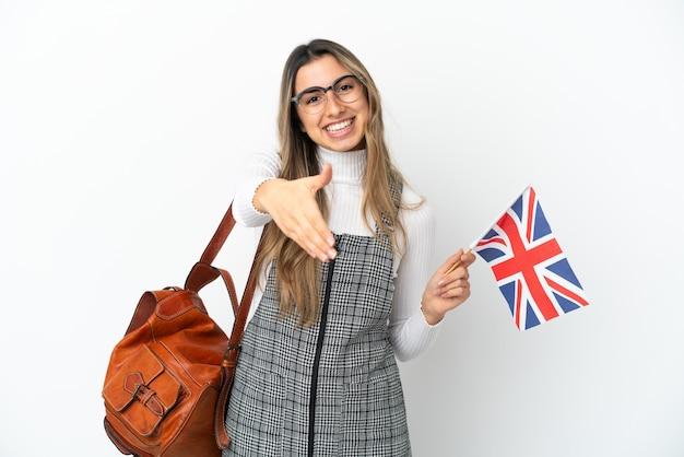 Молодая кавказская женщина держит флаг соединенного королевства на белом фоне, пожимая руку для заключения хорошей сделки