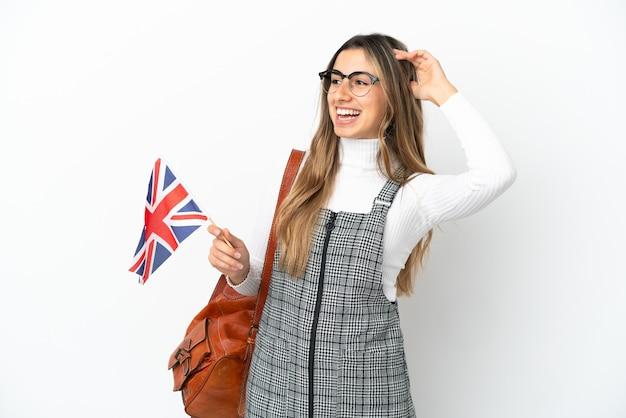 영국 국기를 들고 젊은 백인 여자는 많이 웃 고 흰색 배경에 고립