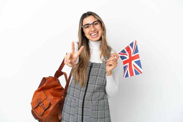 Молодая кавказская женщина, держащая флаг соединенного королевства, изолированная на белом фоне, улыбается и показывает знак победы