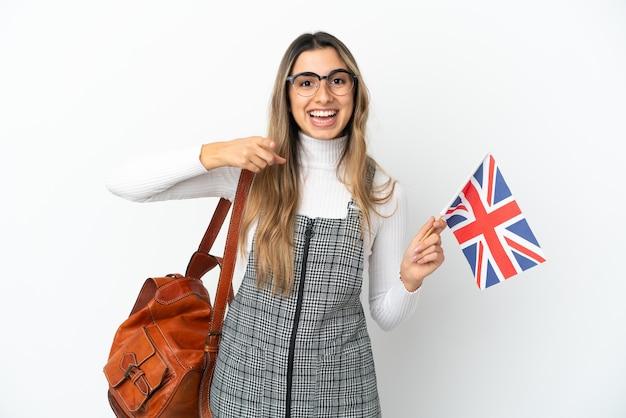영국 국기를 들고 젊은 백인 여자 놀라게 하 고 앞을 가리키는 흰색 배경에 고립