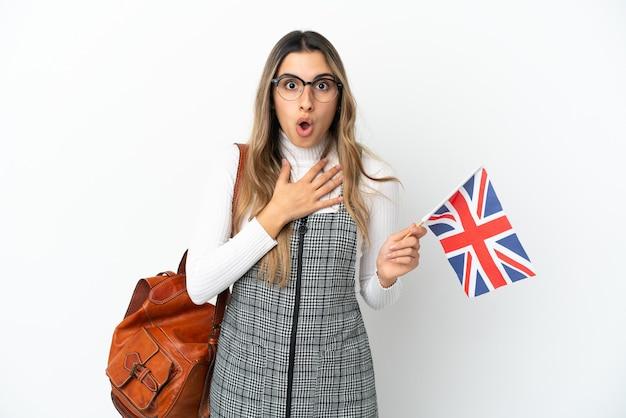 白い背景で隔離のイギリスの旗を保持している若い白人女性は、右を見ながら驚いてショックを受けました