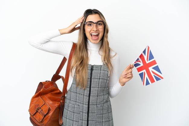 놀라운 표정으로 흰색 배경에 고립 된 영국 국기를 들고 젊은 백인 여자