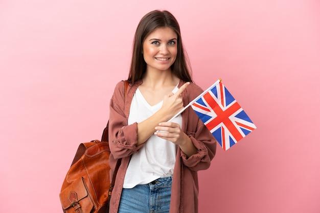 Молодая кавказская женщина держит флаг соединенного королевства, указывая в сторону, чтобы представить продукт