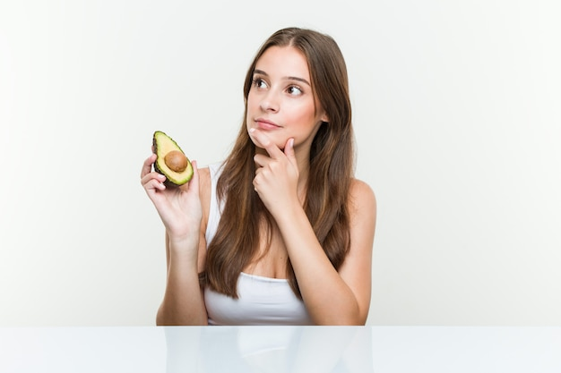 Young caucasian woman holding an avocado looking sideways with doubtful and skeptical expression.