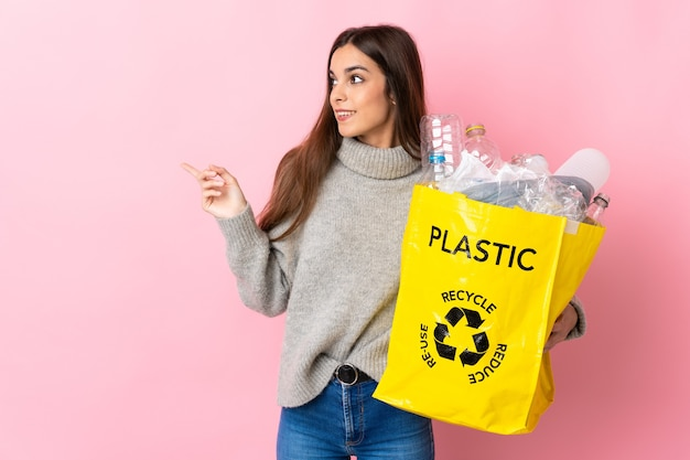 Young caucasian woman holding a bag full of plastic bottles to recycle isolated on pink background pointing finger to the side
