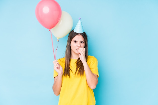 Young caucasian woman holding balloons with worried expression