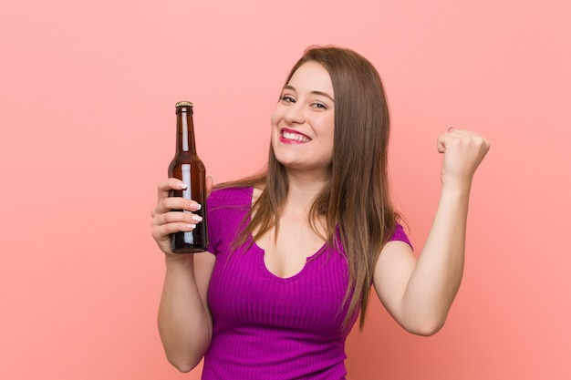 Young caucasian woman holding a beer bottle