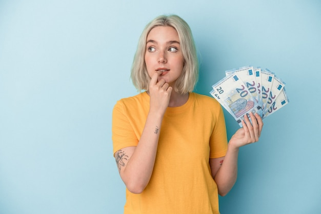 Young caucasian woman holding bills isolated on blue background relaxed thinking about something looking at a copy space.