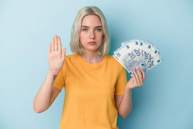 파란색 배경에 격리된 지폐를 들고 있는 백인 젊은 여성이 정지 신호를 보여주며 당신을 방해합니다.
