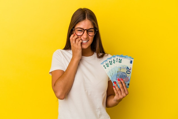 Young caucasian woman holding bills isolated on yellow background biting fingernails, nervous and very anxious.