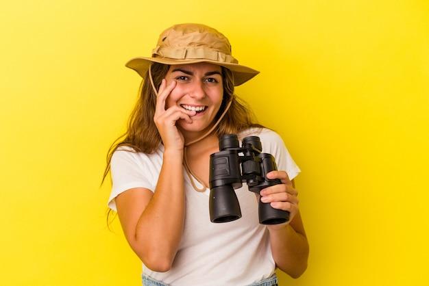 Молодая кавказская женщина, держащая бинокль на желтом фоне, кусая ногти, нервничает и очень тревожится.