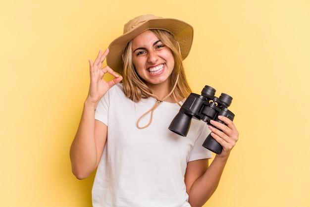 Молодая кавказская женщина, держащая бинокль, изолированная на желтом фоне, веселая и уверенная, показывая одобренный жест.