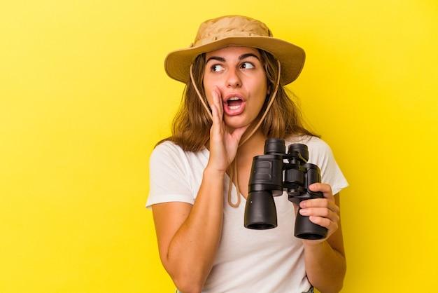 黄色の背景に分離された双眼鏡を保持している若い白人女性は、秘密の熱いブレーキングニュースを言って脇を見ています